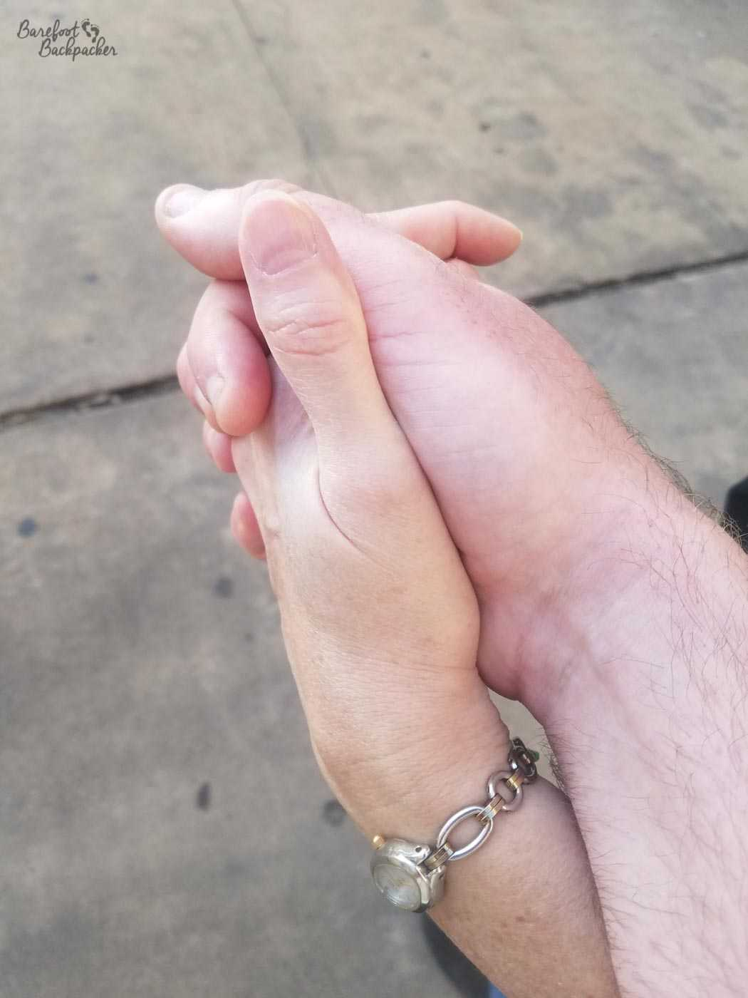 Close-up of two people holding hands in the street.