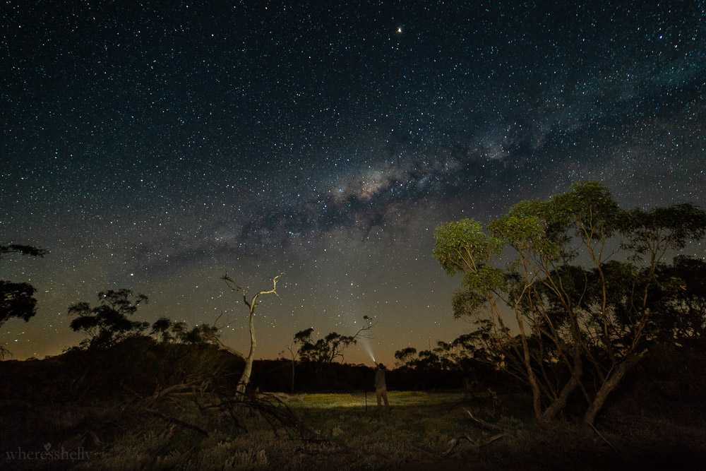 The night sky at Coalseam; view of The Barefoot Backpacker in the middle of the shot, waving a torch. Picture taken by Shelly Tonkin.