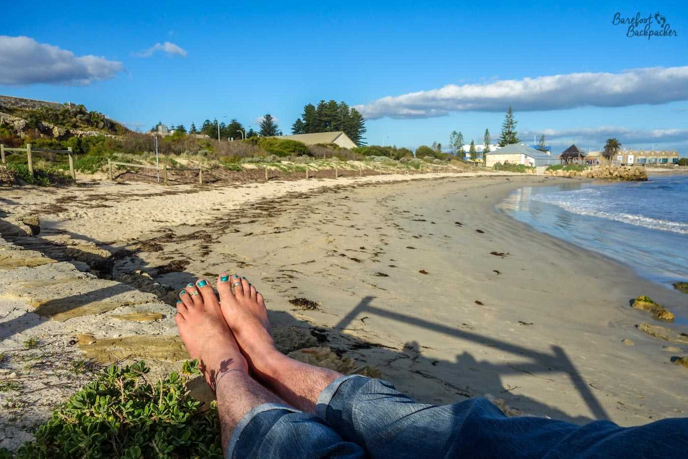 Side view of a beach in Fremantle, with my legs and feet lying on the rocks, across the foreground.