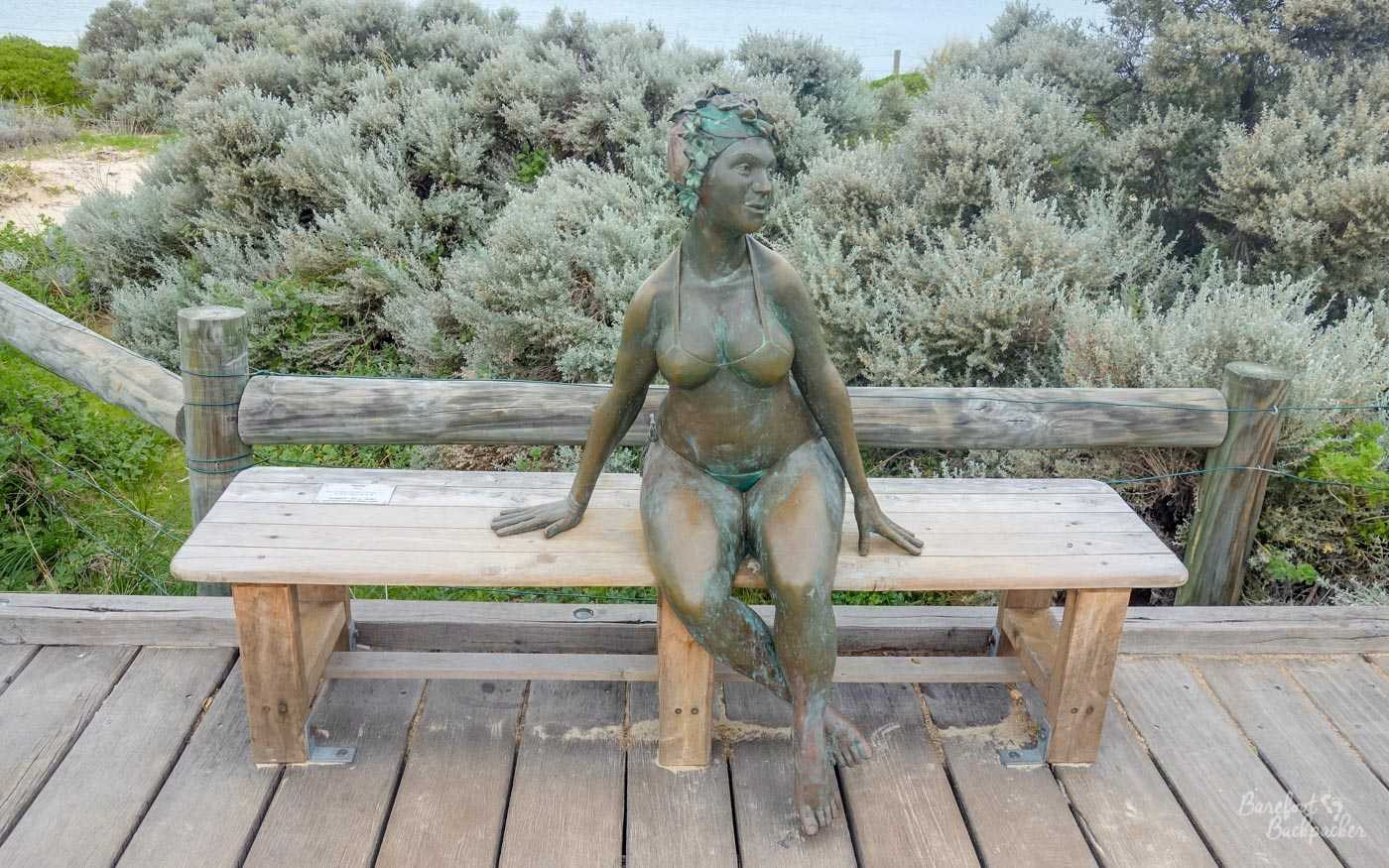 Statue of a woman in a bathing suit sat on a bench. It's called 'Bella', by Greg James.