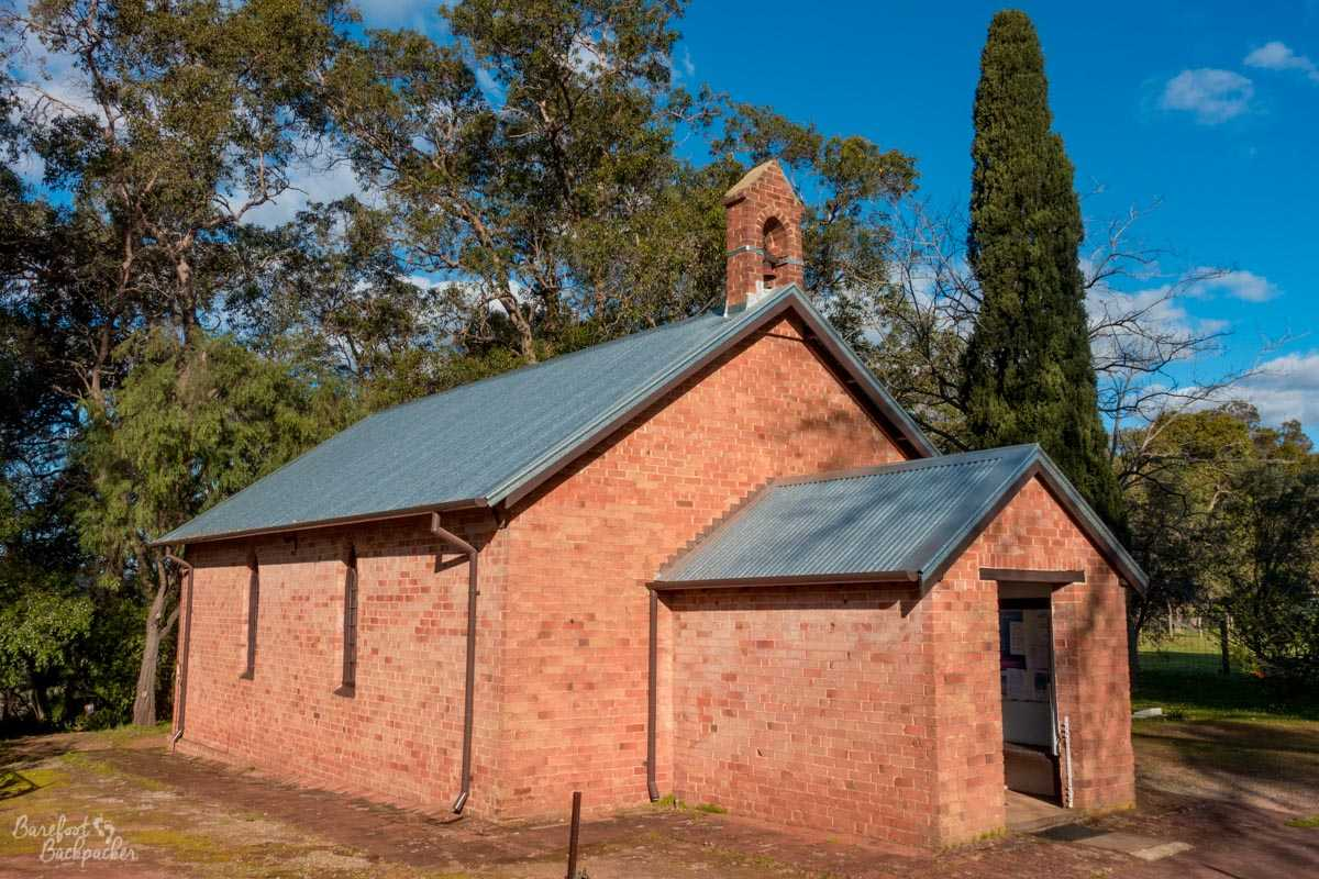 The church building at All Saints, Henley Brook, in the Swan Valley. It's small, consisting pretty much of only one room and a smaller entryway porch. It's made of very bright pale red bricks. There is a very small annexe on top that presumably houses a bell. It's set in a garden with trees behind.