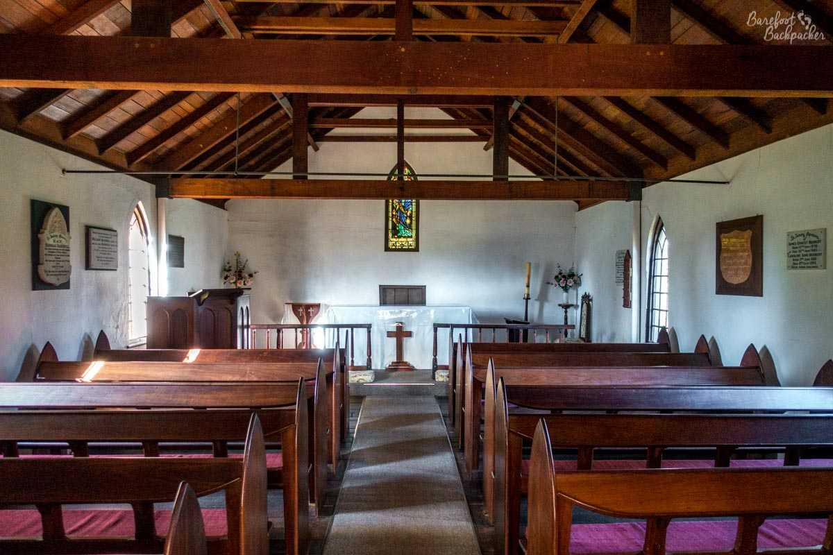 Inside the church building at All Saints, Henley Brook, in the Swan Valley. It's fairly plain, quite white walls, with a small stained glass window on the back wall. Wooden pews, wooden rafters above, couple of plaques on the wall, is all.