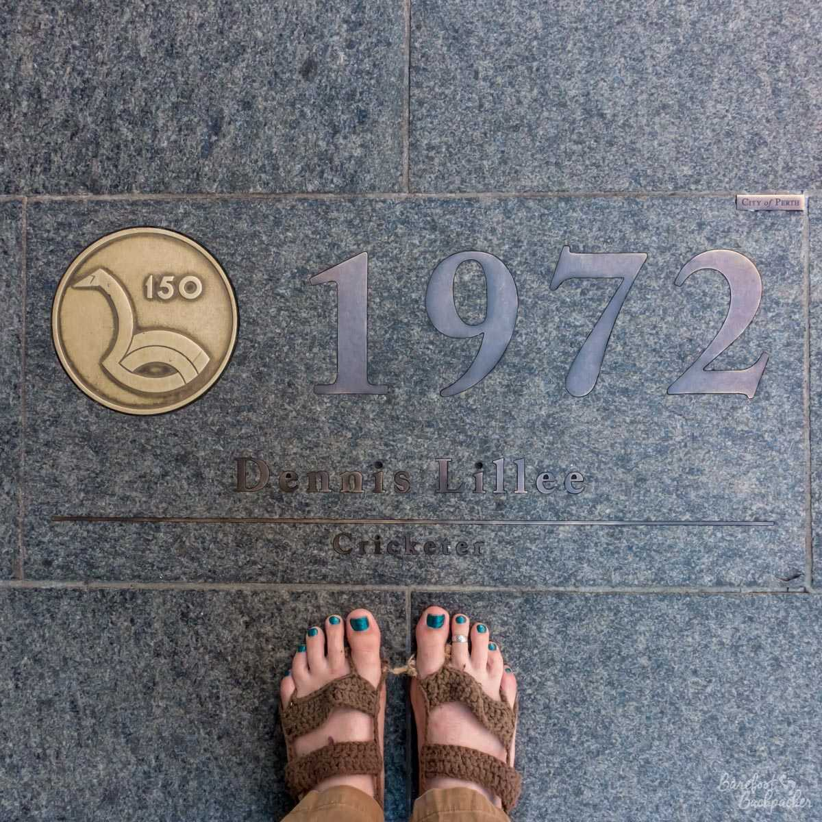The plaque in the Perth walk of fame that commemorates 1972. It's to Dennis Lillie, the Australian cricketer and one of the fastest fast bowlers that ever played. He came from Subiaco, a suburb of Perth. I am standing just below the plaque – a pair of crochet-covered feet with teal toenails standing contrasting against the stone blue of the plaque.