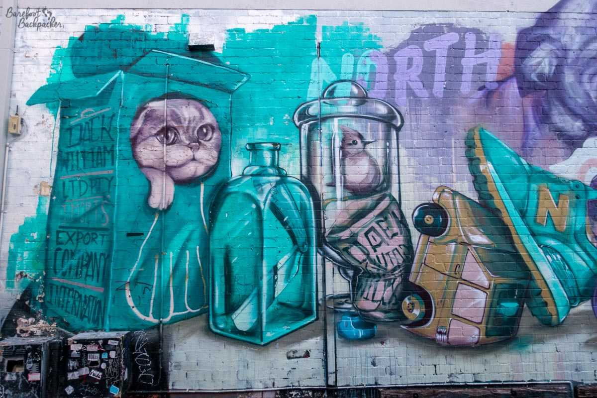 Some weird street art on a wall I came across in Perth in 2018. I've no idea how to even describe it, it's weird, it's got a cat in a cereal box, a potion jar with a flick-knife, a bird in a cylindrical jar, a crushed can, and someone's foot in a sneaker/trainer pushing half a car into the pavement.