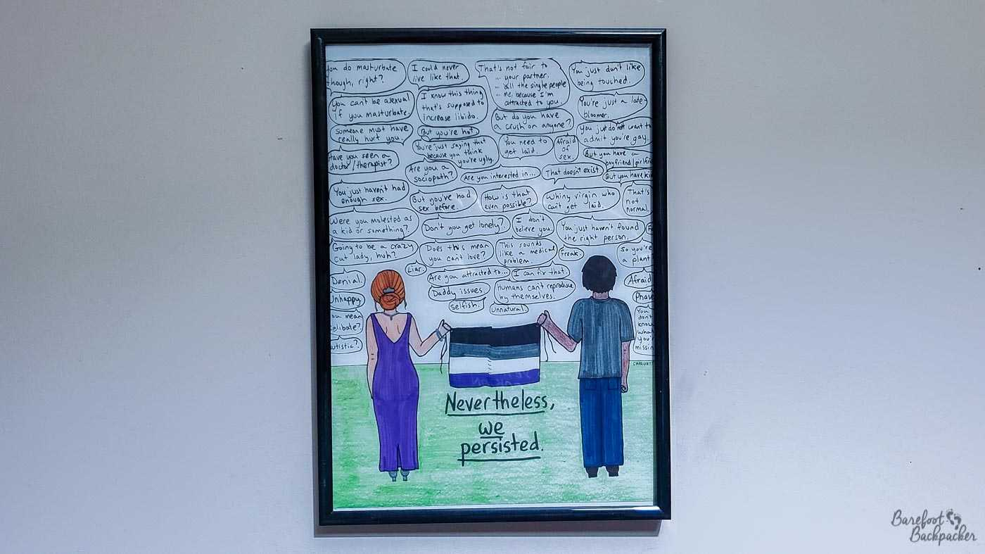 A poster I bought from 'keep_persisting' (Courtney Privett) on the website Zazzle. It shows asexual awareness, and depicts two people, backs to camera, holding an asexual pride flag above the caption 'nevertheless, we persisted'. The entire top half of the poster is littered with speech bubbles with acephobic comments like 'you need to get laid', 'this sounds like a medical problem', and 'freak'.