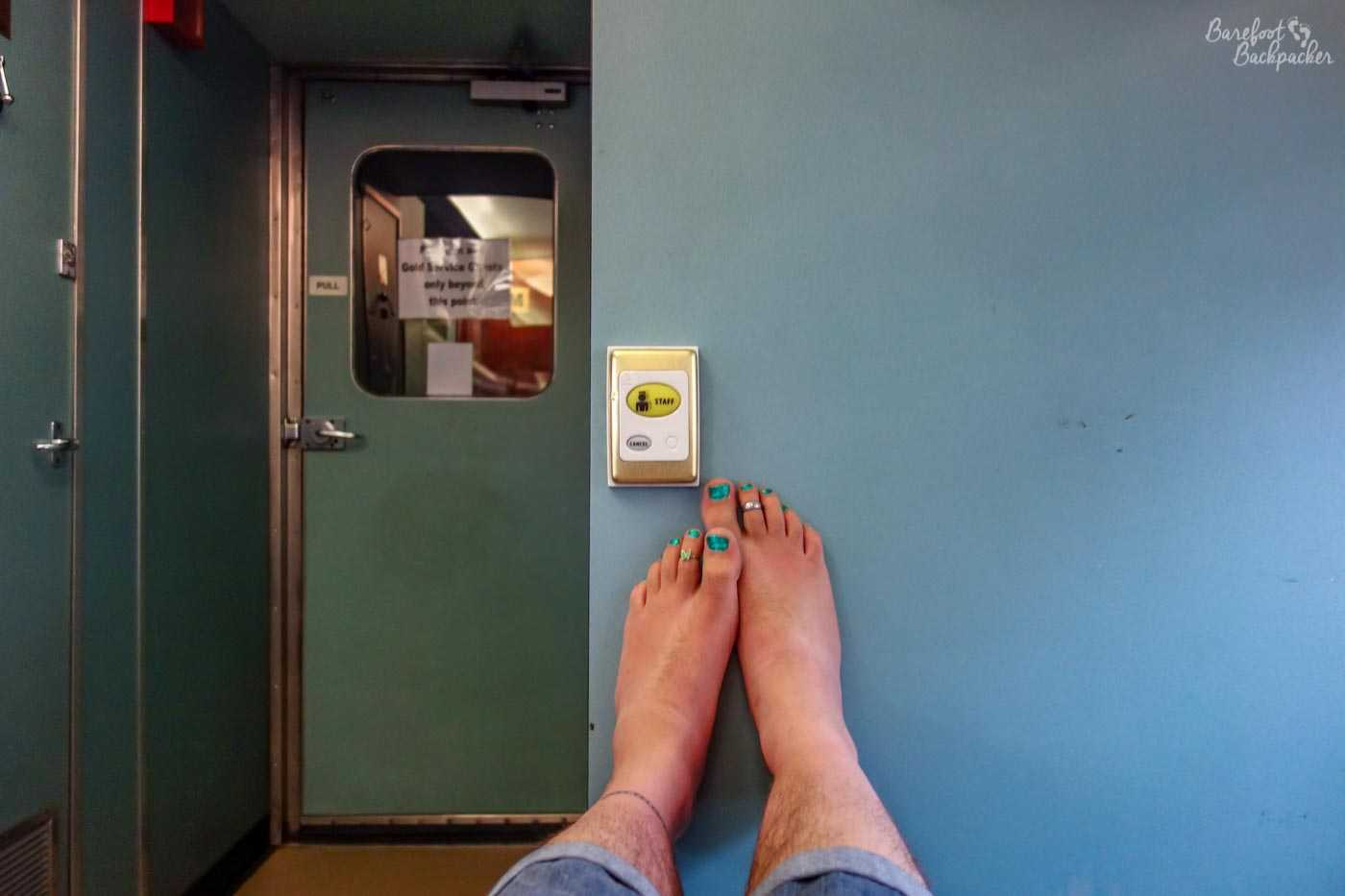 Two bare feet resting on a plain blue wall. To the left is a door that says 'Only Gold Class Ticket Holders Only'.