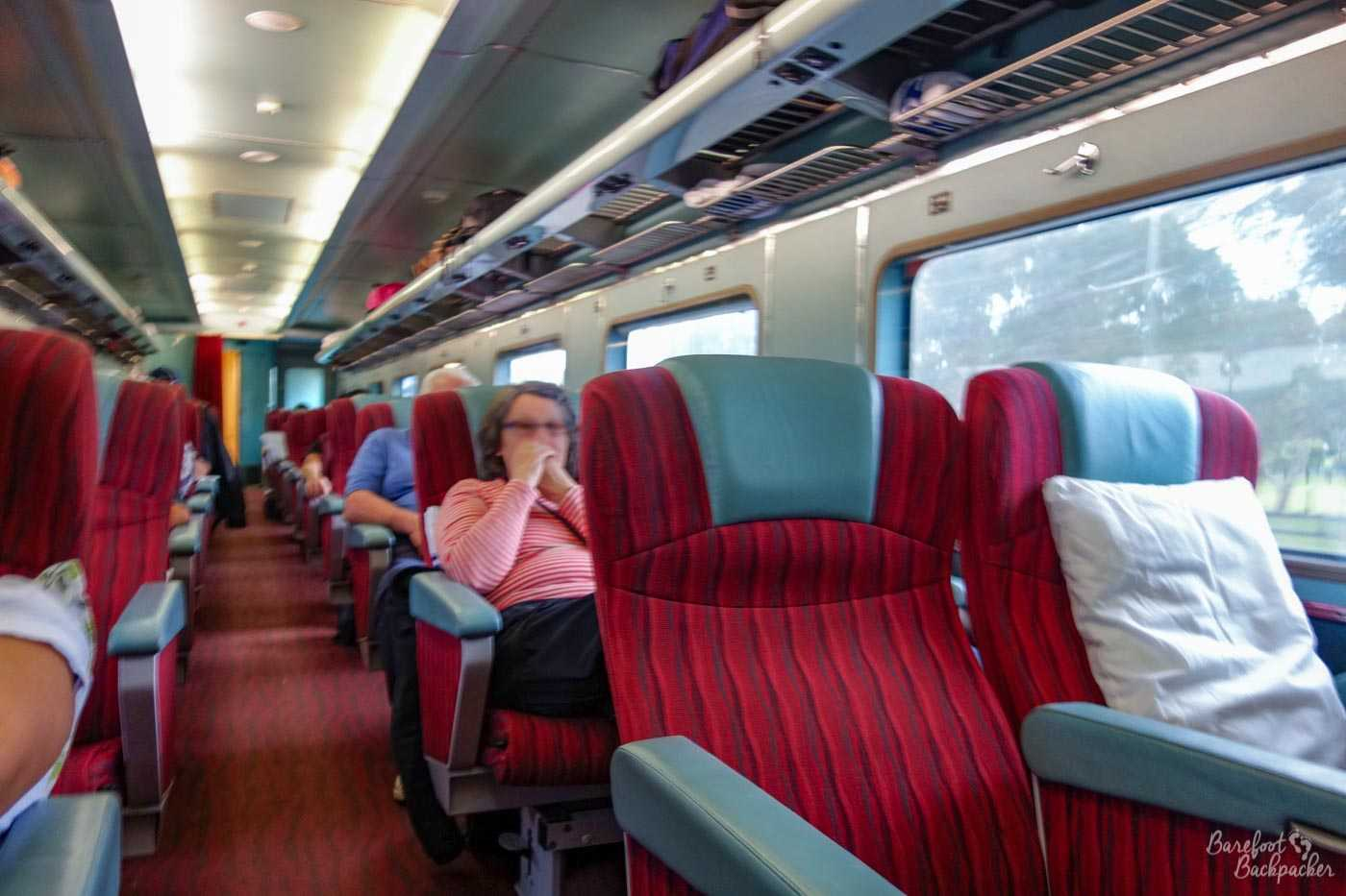 Inside the red Class carriage of the Indian Pacific. Looks a bit like a normal train carriage, with rows of seats separated by an aisle. Just more space between them.