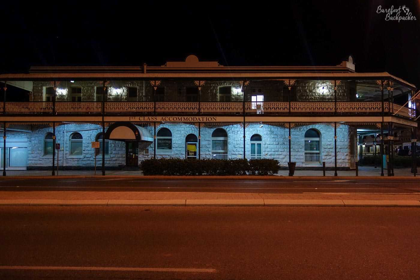 A hotel in Kalgoorlie, over the road. Picture taken at night. White stone walls. It has a balcony type thing attached to its whole upper floor; iron-wrought and see-through, like you find in late 19th-century American buildings.