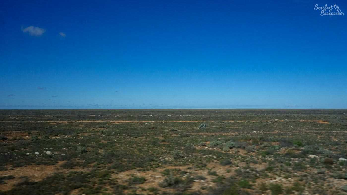 The Nullarbor Plain. Flat, scattered small short shrubs amid dusty yellow/orange sandy soil, under an unforgiving blue sky. For a day.