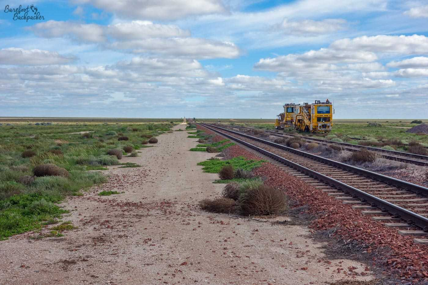Siding at Cook Railway Station. There's a train engine thing in the distance, otherwise it's flat, featureless, and and endless – the railway line goes straight towards the horizon.