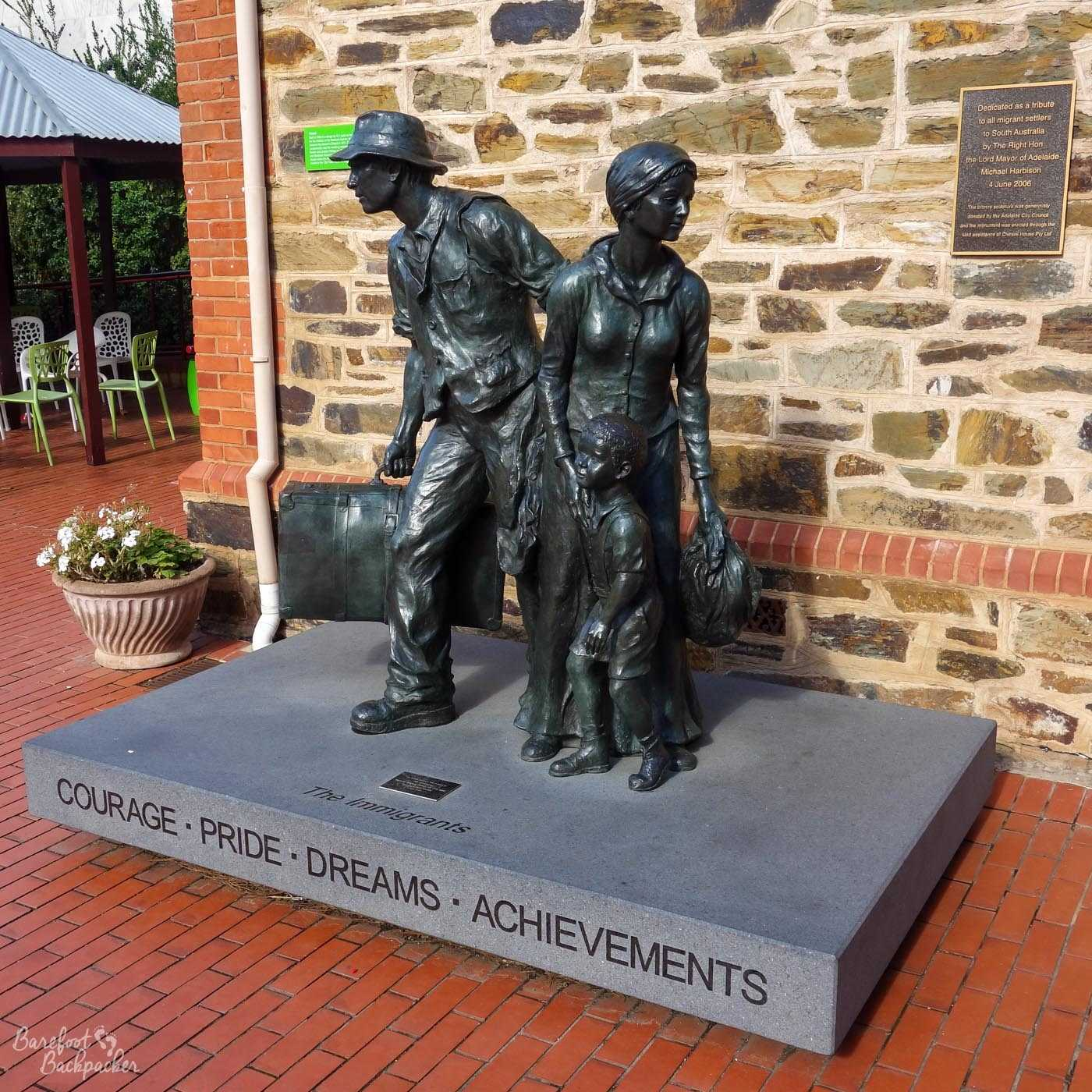Statue of an immigrant family – father, mother, one kid - outside the Migration Museum. The caption below them says 'Courage. Pride. Dreams. Achievements.'. The plaque on the wall behind says 'Dedicated as a tribute to all migrant settlers to South Australia'. What it does not specify is the … preference for the type of immigrant, but that's a story for another post.