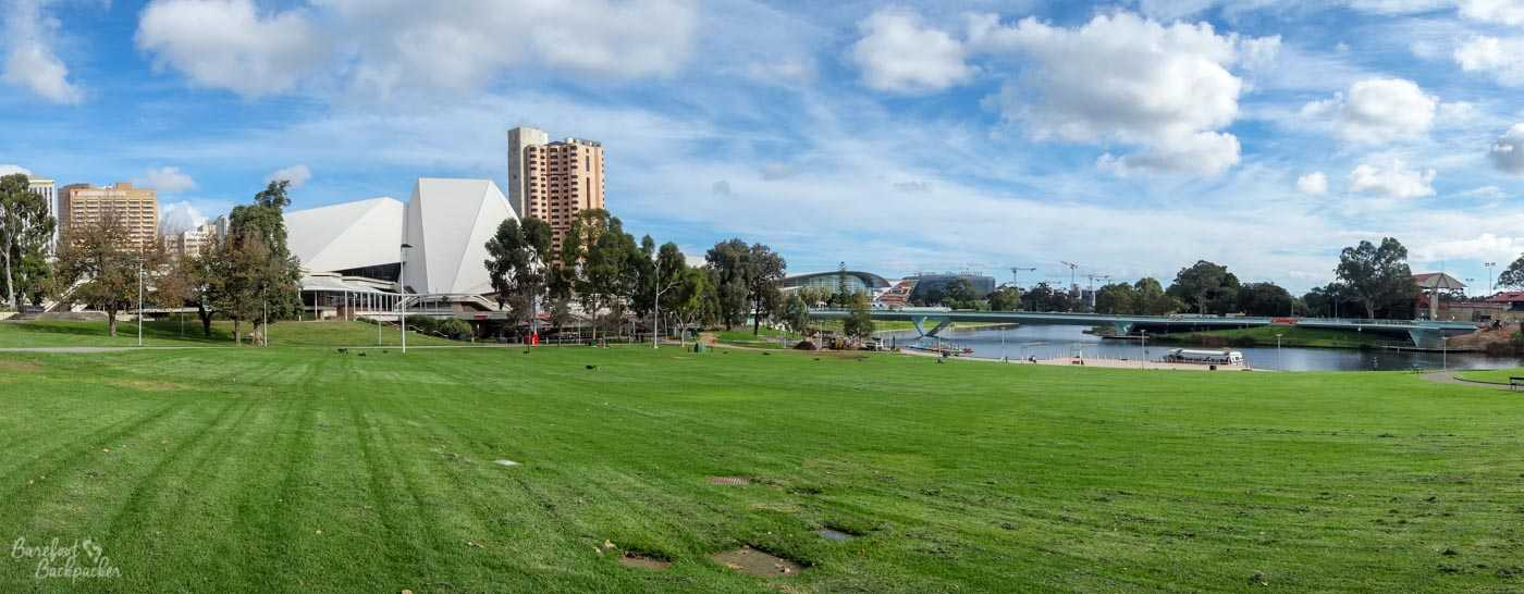 One of the parks that encircle the city centre of Adelaide – a green sweatshirt around the city. This one is near to the river. Lots of grass by the waterfront with buildings in the distance.
