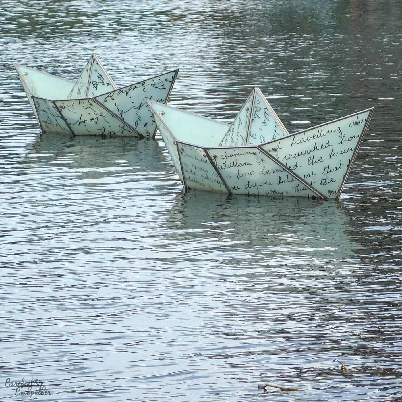 Two small boats that make up the 'Talking Our Way Home' public art piece. They lie in the middle of the river and are in the form of origami boats, and look quite fragile and precarious. On them is written writing but from this distance I can't make out what they say.