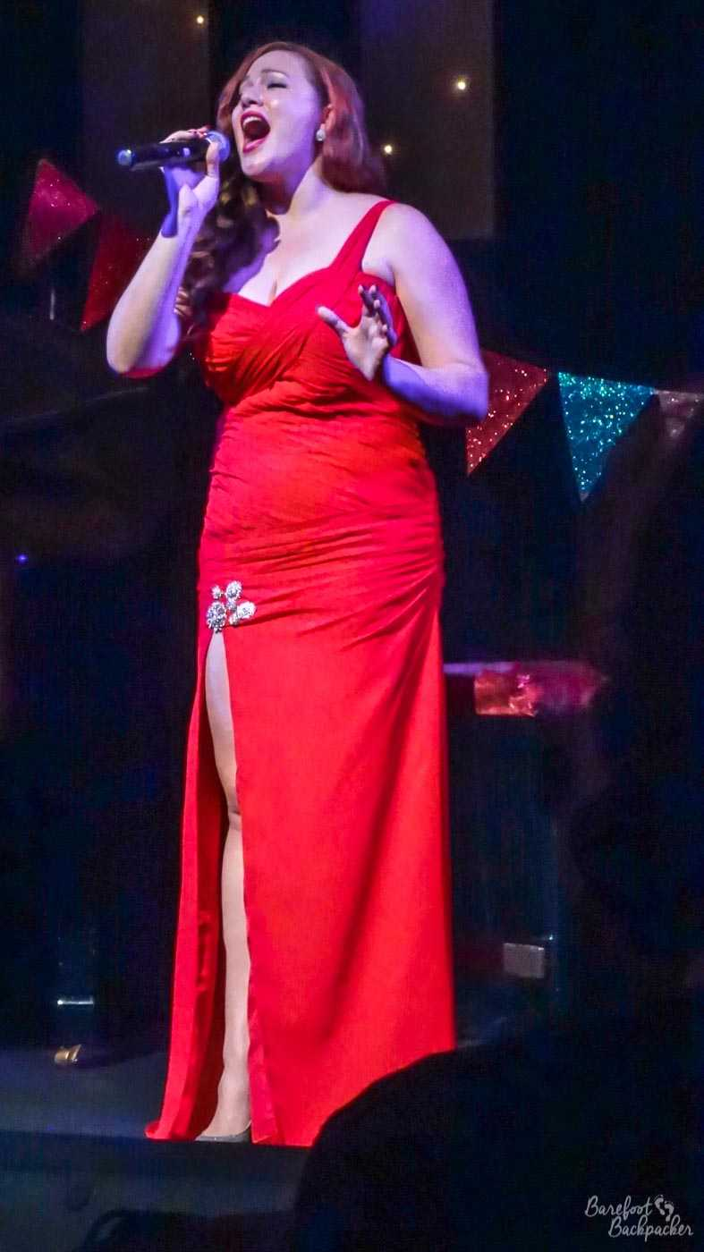 Carla Conlin, on a dark stage, in a long red dress.