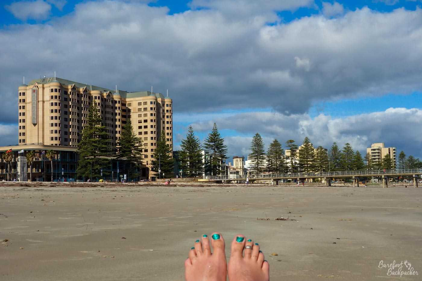 The beach at Glenelg, looking back towards the town. It's sandy. There are bare toes at the bottom of the shot. Because it's a beach and people who wear shoes on a sandy beach are weird. There, I said it.