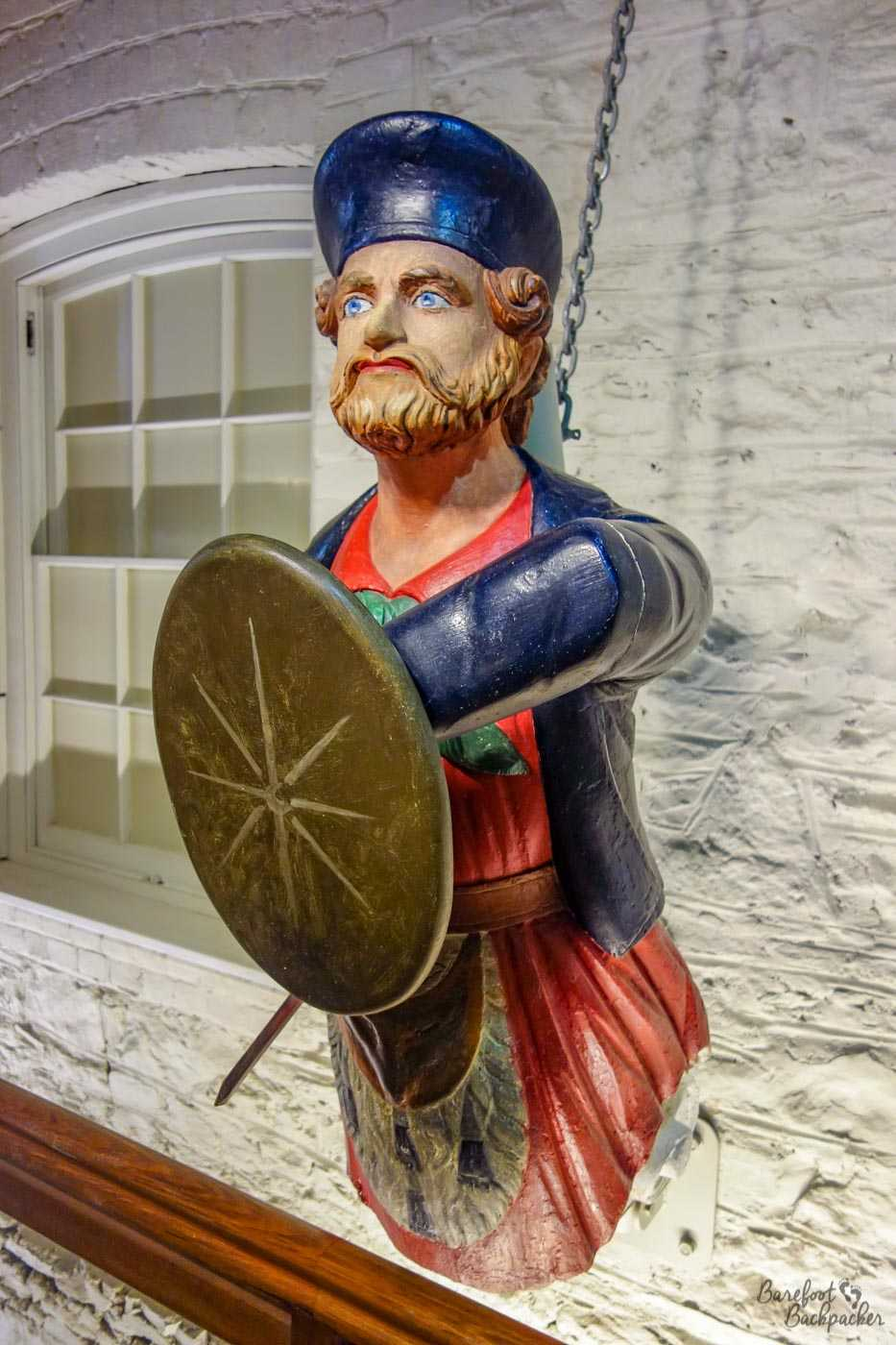 A ship's figurehead on the wall of the Maritime Museum. The museum has quite a number of these; this particular one is of a bearded man with blue hat, red tunic, and holding a shield in front of him.