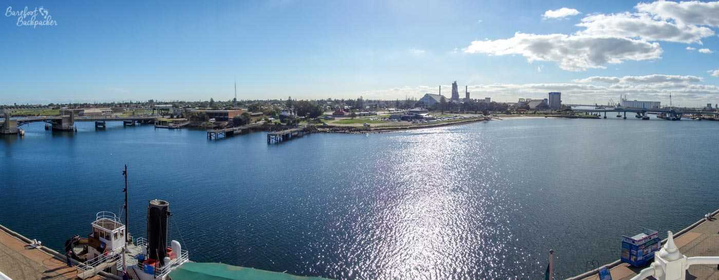 A view of Port Adelaide taken from the top of the lighthouse tower thing, looking out over the water. There are landing spots for ships on both sides of the water, and some bridges and buildings (including a church) visible beyond the harbour area.