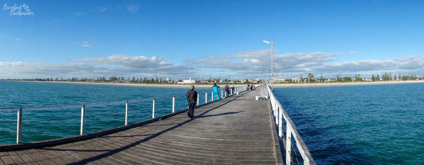 A view of Port Adelaide taken from quite a way along the jetty. The town is a distant gaggle of buildings. Most of the shot is the blue water of the ocean inlet, punctuated by the wooden slats of the jetty fading into the distance.