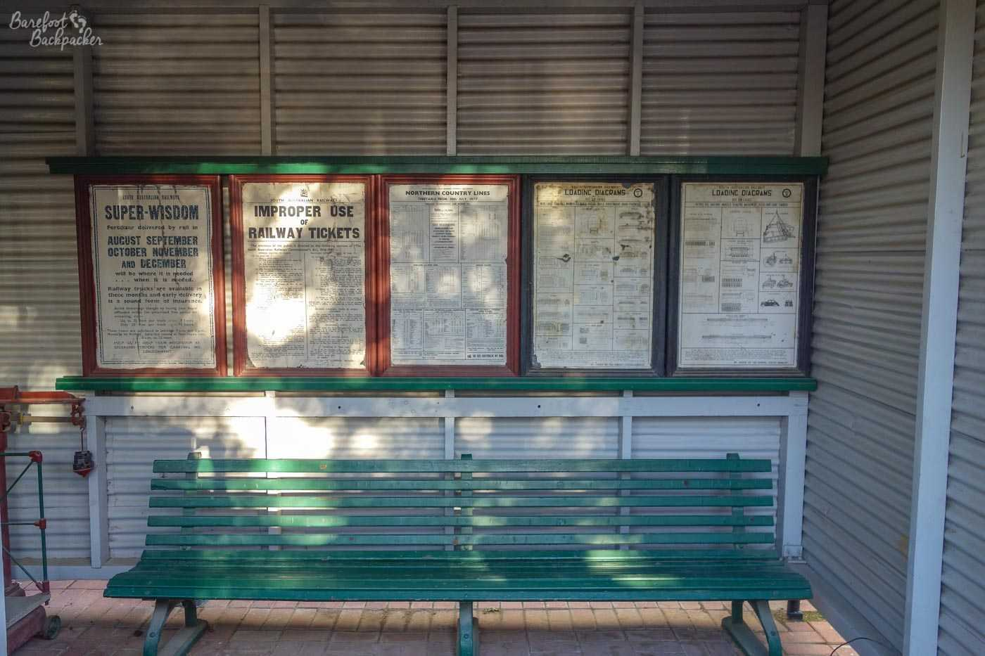 A replica of a waiting shelter at a railway station. There's a green wooden slatted bench below a series of old-fashioned information posters including timetable information, freight loading instructions, and the rules and regulations on the use of railway tickets.