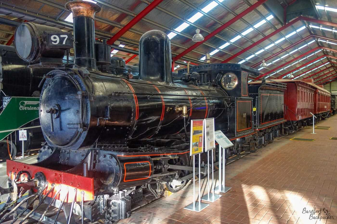 A black railway steam engine (given the number '97') in situ inside the railway museum, complete with tender, and pulling two brown old-fashioned carriages. I can't see the front wheels properly so I can't tell the configuration of the engine but I'm guessing it'd be a 4-6-0 or a 4-6-2.