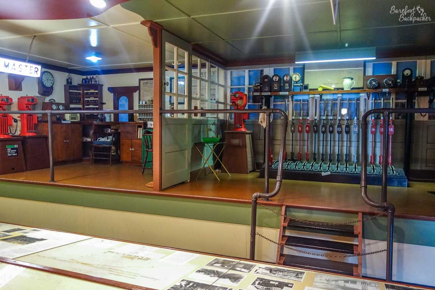 Replica signal box and stationmaster office, in the railway museum. On the left hand side is the stationmaster's office, with weighing machines, post sorting boxes, a desk, a large clock, and what appear to be a suspiciously large number of glass bottles. On the right is the signal box, mostly made up of sixteen huge numbered leavers (we're talking maybe over a metre in height) that would have operated either the signals or the railway junction points. In the background are some weird devices noted as 'block indicators', 'track indicators', and 'timers', but look for all the world like barometers – boxes with arrows in them. I have no idea. I'm not a signalman. There is also, even more oddly, a bird-cage, complete with bird(s). Whether bird cages were a traditional feature of signal boxes in Australia, or whether that was the only place the museum could find to put it, I couldn't say.