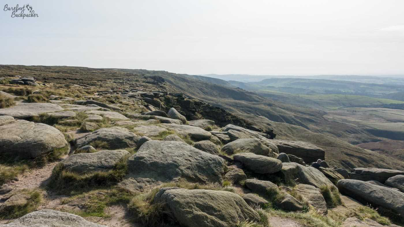 A landscape vista across the edge of Kinder Scout, near Kinder Downfall. In the foreground, on the ground, are a series of fairly smooth, irregularly-shaped, grey stone boulders. These continue into the distance along the edge of a cliff. To the left, the land slopes gently upwards, and is mainly level and covered in low shrub and moss. To the right the land slopes away sharply downhill, revealing distant hills and valleys, looking a little teal rather than green, because England. The sky is fairly bright but completely covered in white cloud.