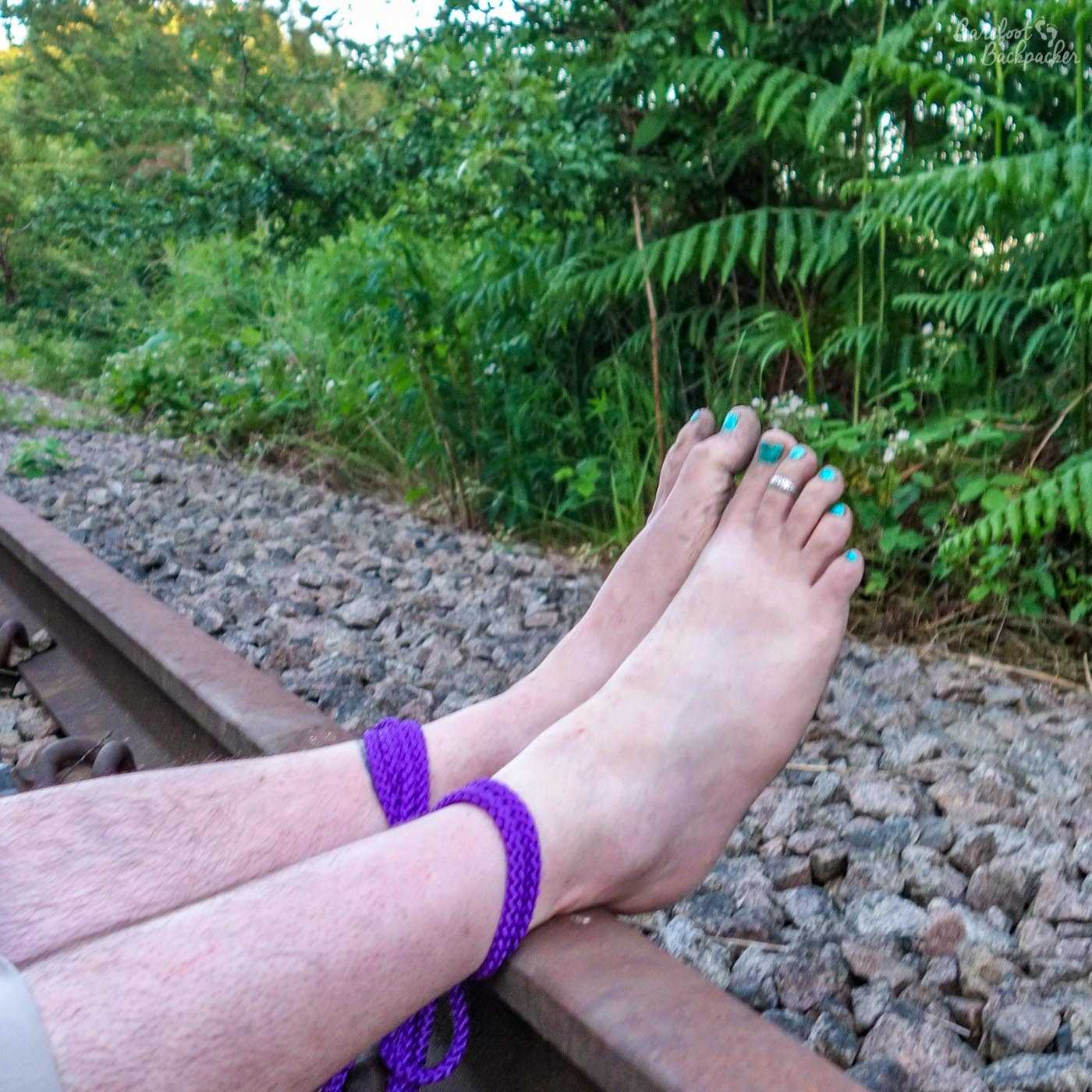 A close-up of two bare feet tied to a railway line. It's a bit overgrown.