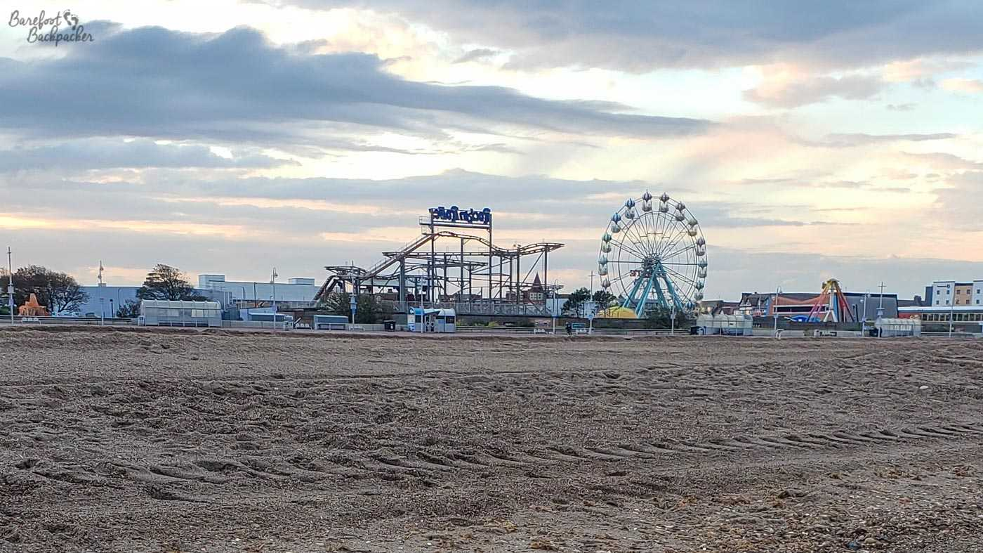 An example of one of the British Seaside Resorts. This is Skegness Beach, heading towards dusk. There is a big wheel and a rollercoaster visible in the background, set against a greying sky, while the foreground is a gentle slope of thick sand.