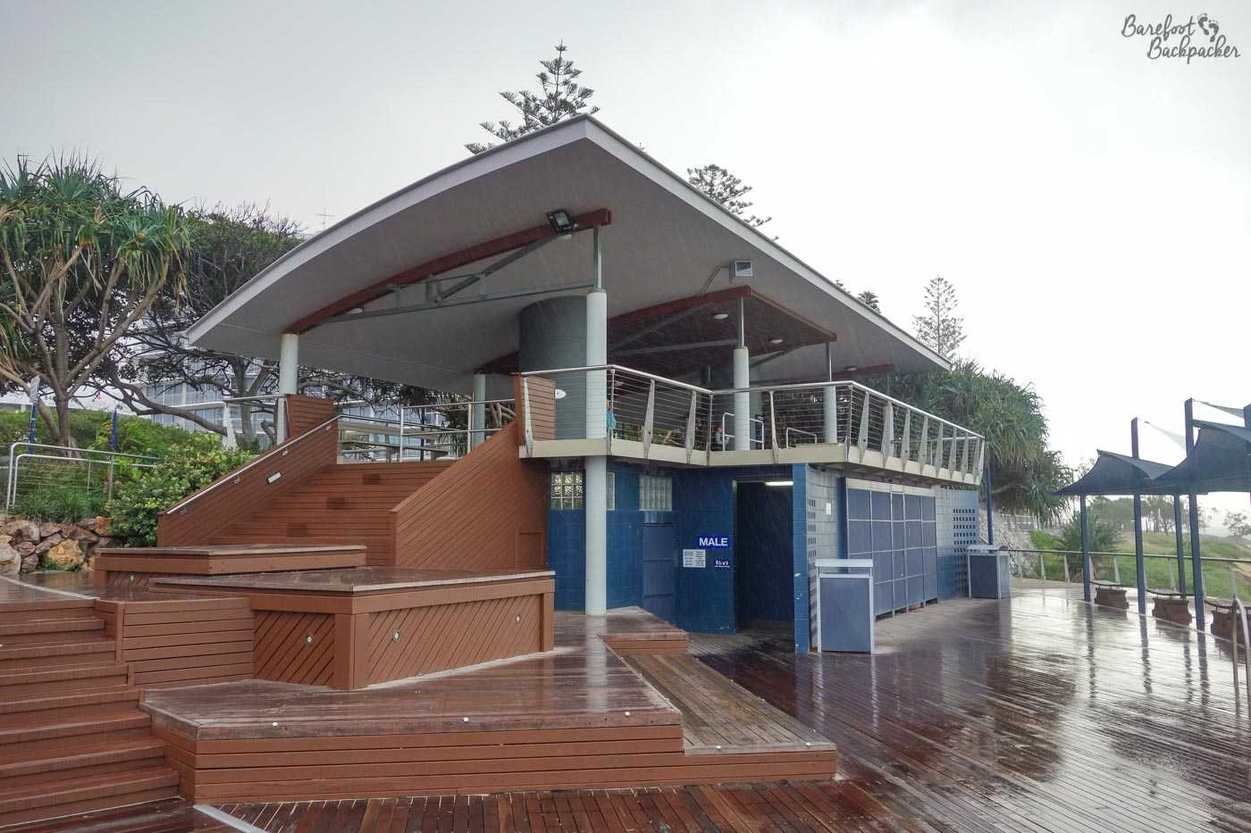 Frontal view of the seafront toilets, the 'loo with a view', in the rain. It's built on a couple of levels, with wooden decking leading up from the toilets themselves to the lookout section above, which is underneath a canopy. It looks a little like a modern bus station, if we're being honest.