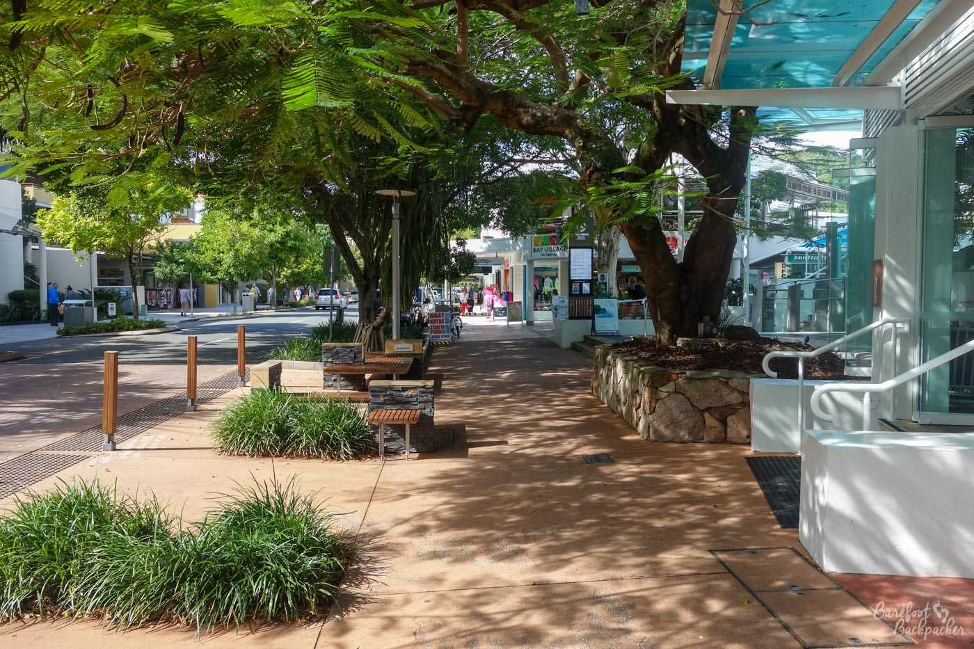 Shot of Noosa town centre. Quite which of the Noosas, I couldn't honestly say, but I assume it is Noosaville. Shops and trees on both sides of a road. It's … not anything particularly unusual?