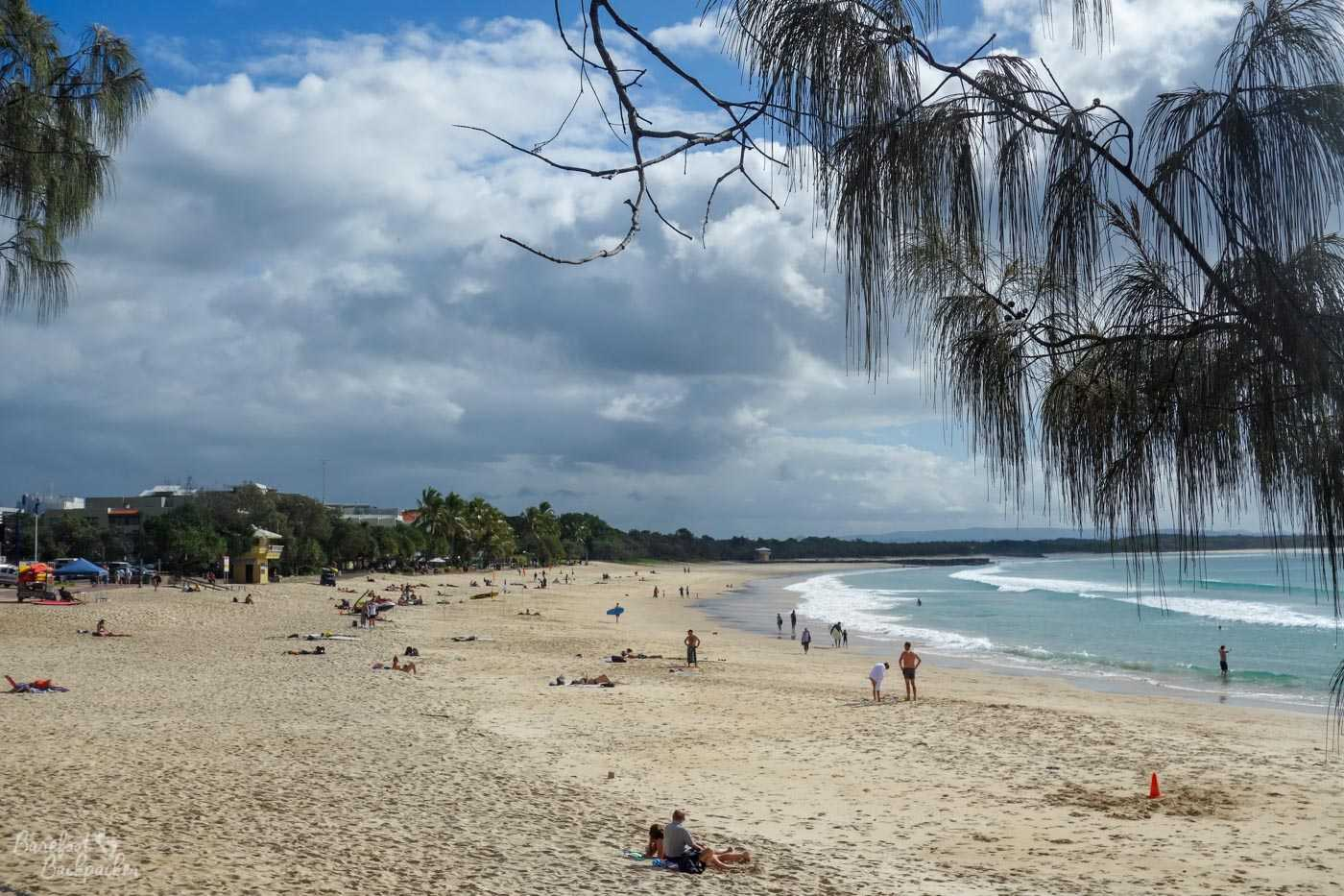 The beach at Noosa. It's pretty wide, yellow, sea on the right, trees hiding the prom on the left, lots of people on the sand, a couple holding surfboards.