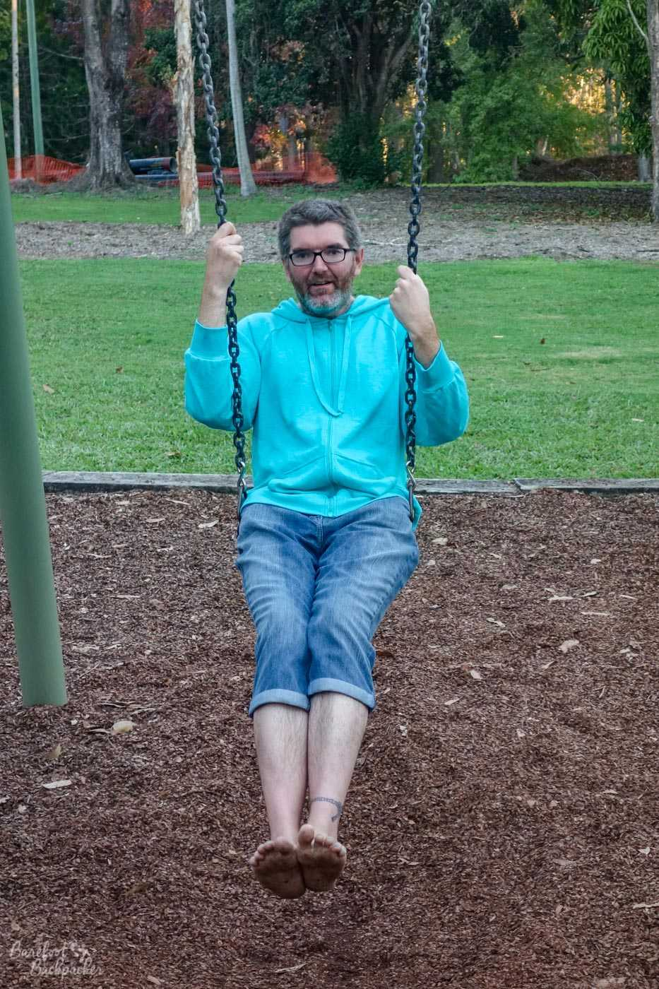 Man pretending he's still a child by playing on the swings. Barefoot, obviously.