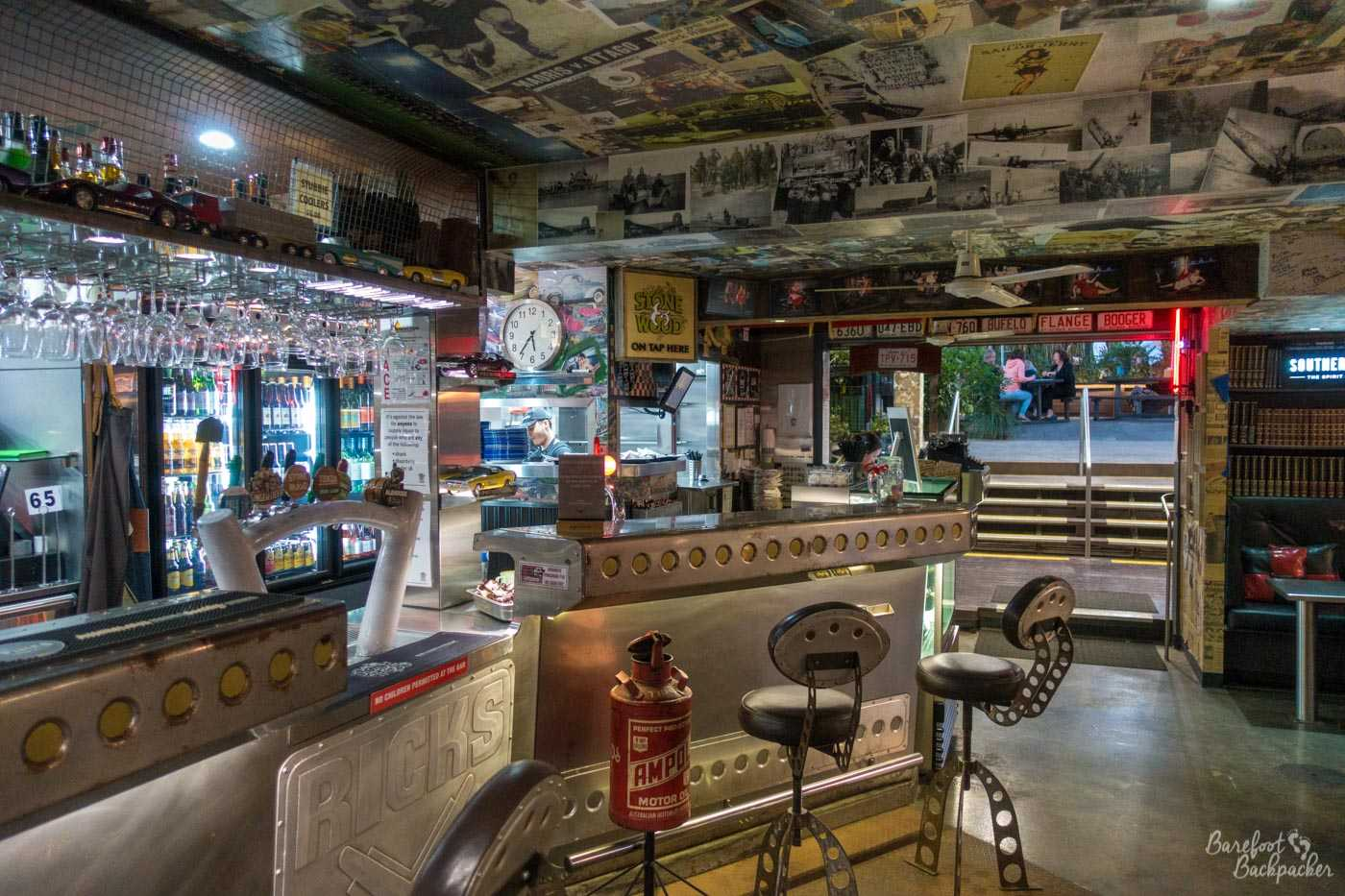 The inside of Rick's Garage in Palmwoods. Metallic chrome effects everywhere, pictures and newspaper cuttings on the ceiling and the walls. 1957 called ...