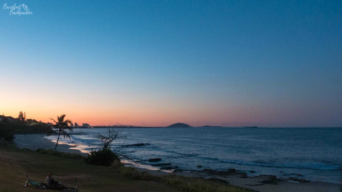 Sunset at Mooloolaba beach. The land curls round to the right and in the distance is the distinctive mound of Mount Coolum, the obvious peak in a flat vista. The sea to the right doesn't have hills in it either. Because it's the sea.