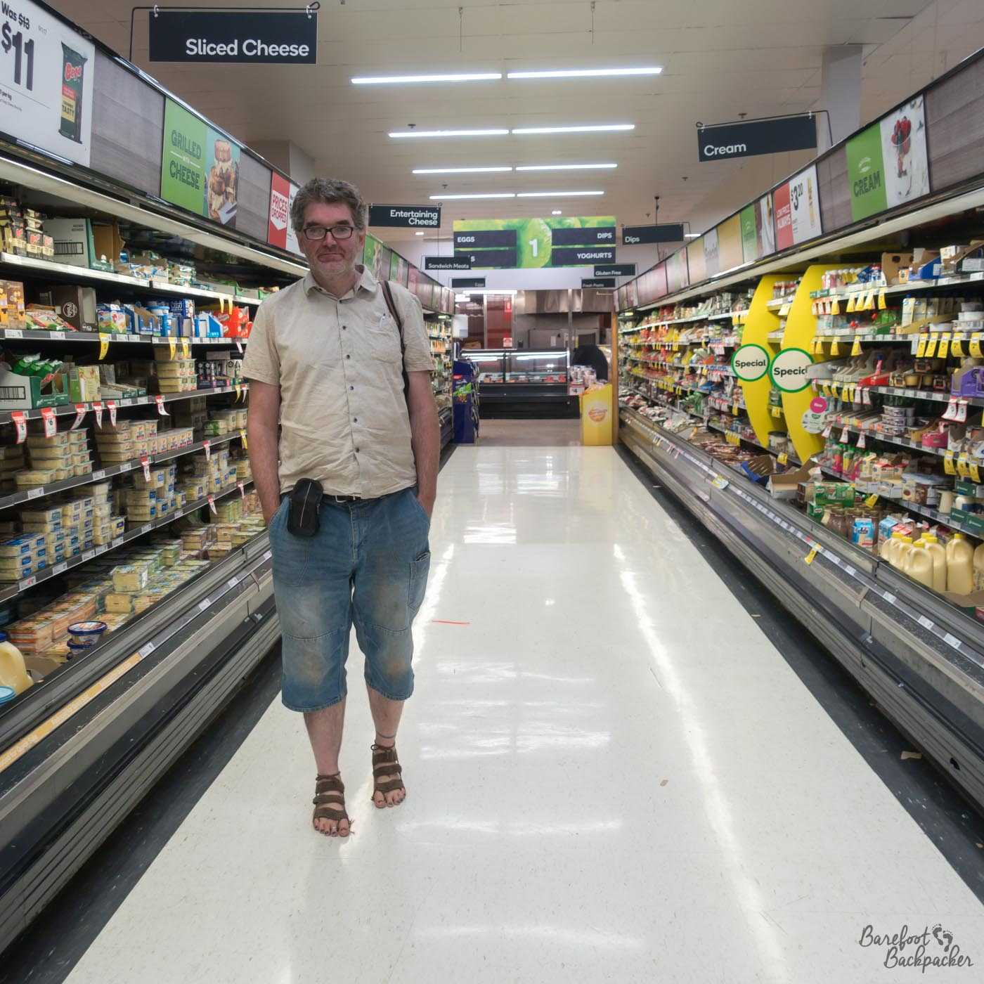 The Barefoot Backpacker standing barefoot (those are crocheted sandals but have no bottom), in short-sleeved shirt and Capri-length denim trousers, in a supermarket aisle. It's the cheese & butter aisle. He doesn't come across as being impressed.