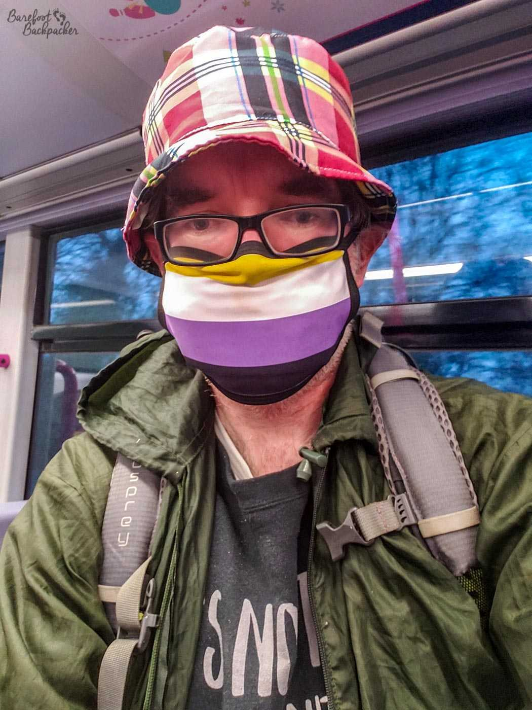 Man (though YMMV on that) sitting on a tram in front of a window. They're wearing a plaid hat (mostly red), a green cagoule, a backpack (full of shopping but you don't need to know that), and a face-mask with yellow, white, purple, and black stripes.