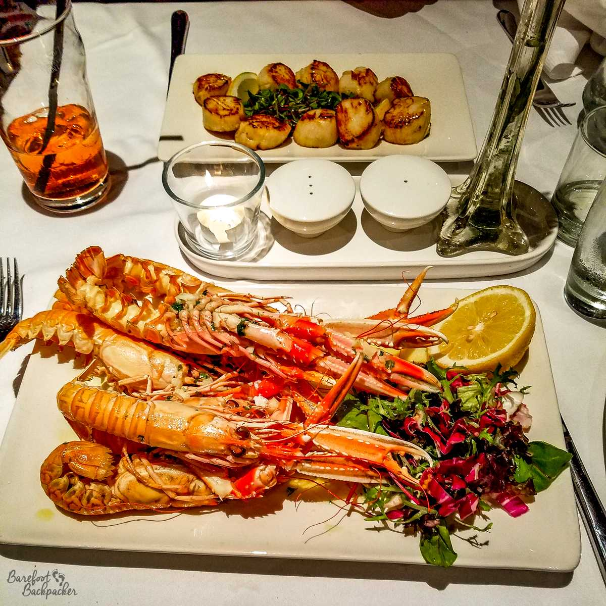 Seafood at a restaurant on Loch Fyne. It mainly consists of several langoustines, wider than the plate they're served on. There are also a plate of scallops, salad, lemon, and whisky in shot.