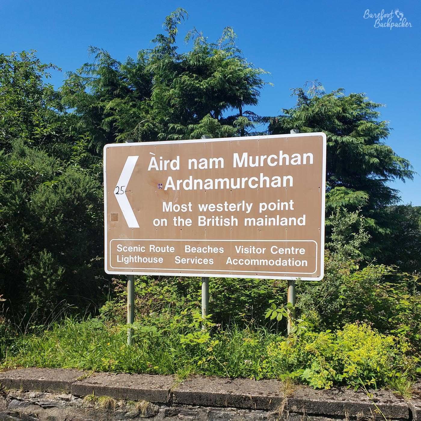 Large brown signpost directing people to 'Ardnamurchan, most westerly point on the British mainland', giving details of some of the facilities (beaches, lighthouse, accommodation, etc).