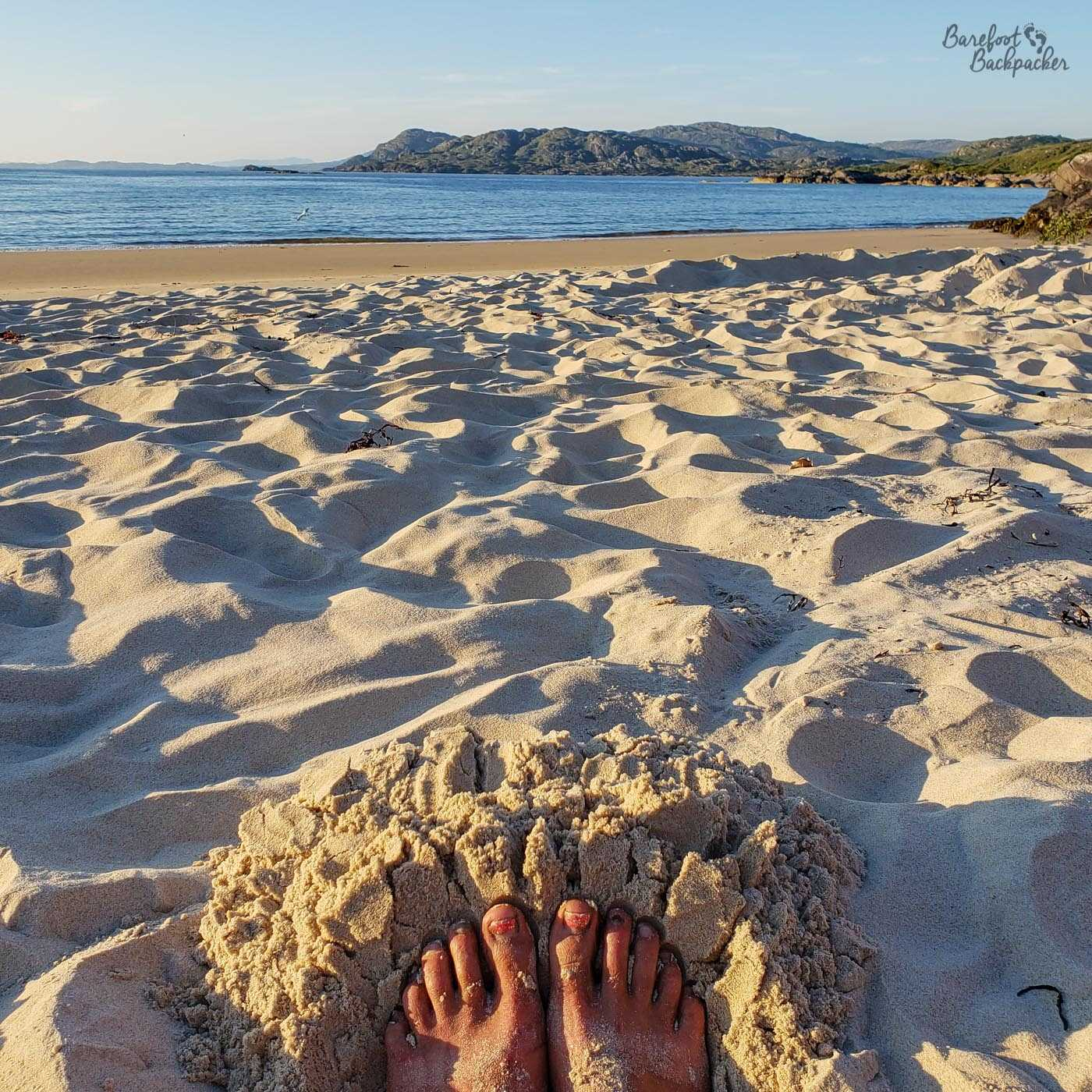 Sandy toes with red nail varnish are pushed against a small bank of sand in a hollow. The sand stretches out above until the sea, the rocks behind, and the blue sky are visible. The sun is shining on the feet and the sand, brightening everything in the mid-evening.