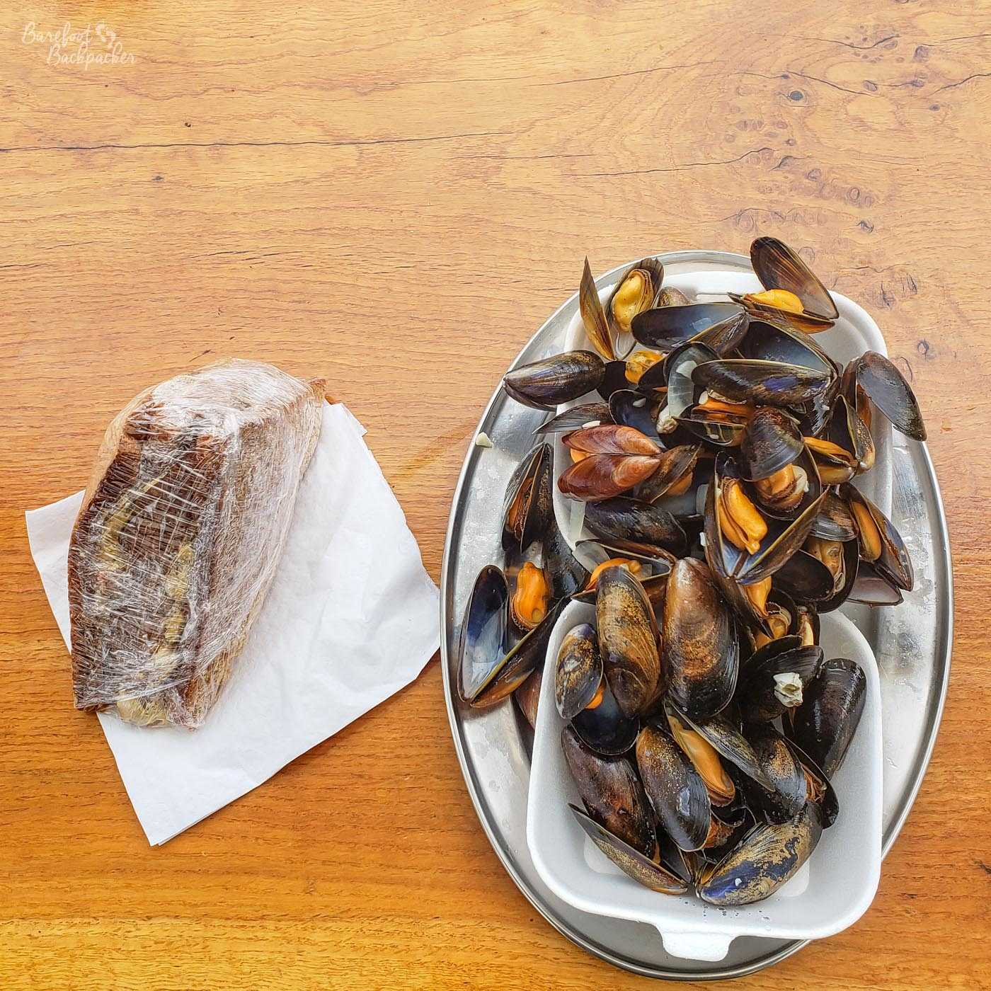 Mussels in a bowl, and a wrapped selection of prawn sandwiches, on an outside table at Oban ferryport.