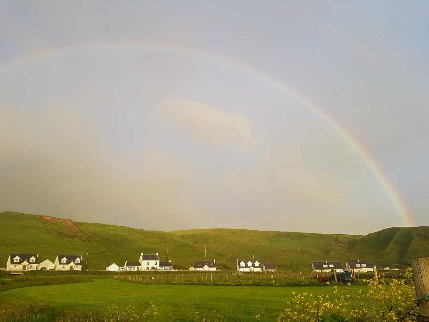 About ten buildings, with gaps between some of them, stand low and are almost hidden by the large green hills in the background. The sky is wide and slightly cloudy, but a huge rainbow arcs above the village.