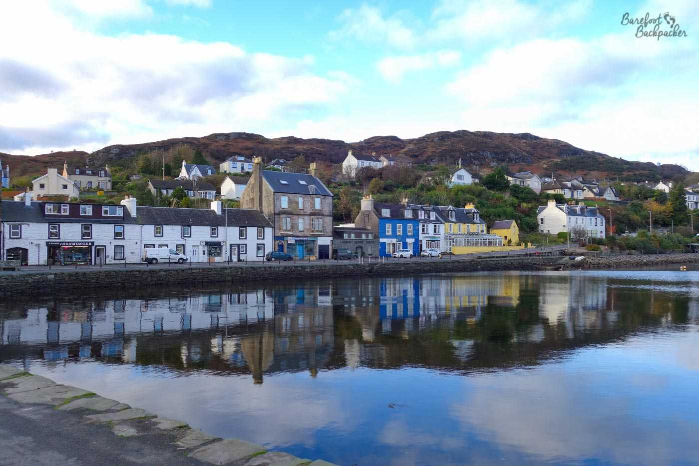 Colourful buildings at the edge of the harbour at Tarbert. Behind them the land rises up a hill range. The reflection of the buildings is visible in the slightly rippled but otherwise flat water.