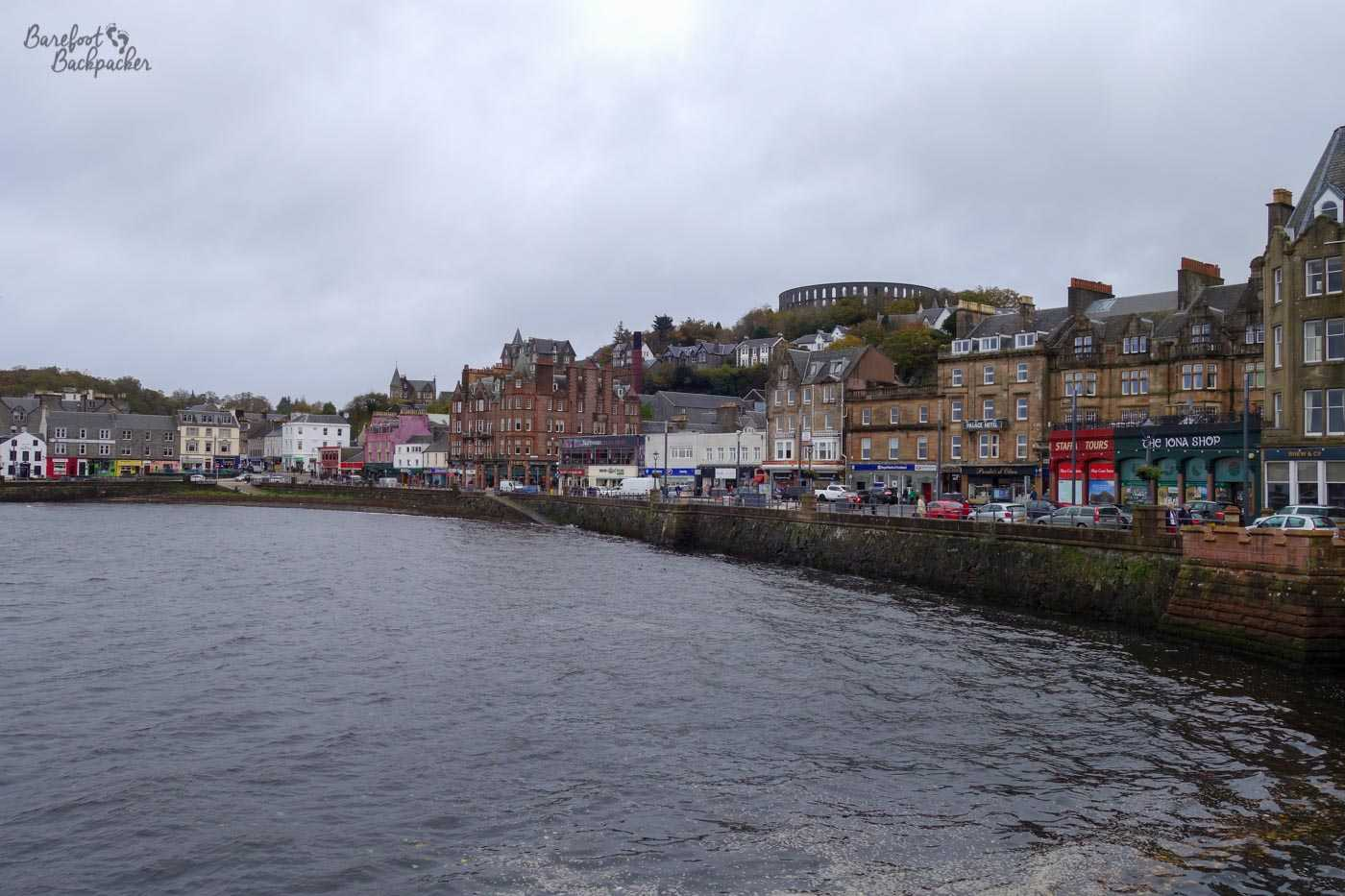 The waterfront at Oban. The water in the bay brushes against a brick sea wall, behind which is a road lined with brick buildings three of four storeys high. The land rises to the back and there's a weird circular structure with arches in the background at the top of the hill.