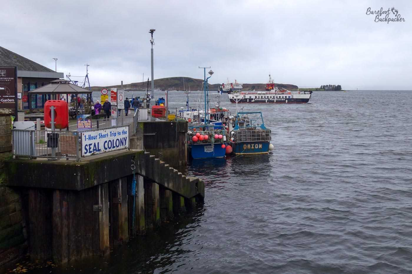 A jetty at Oban. There's a couple of boats on the water that might be going to a seal colony, as a large sign on the sea wall advertises. In the background is a ferry going to one of the Inner Hebridean islands.