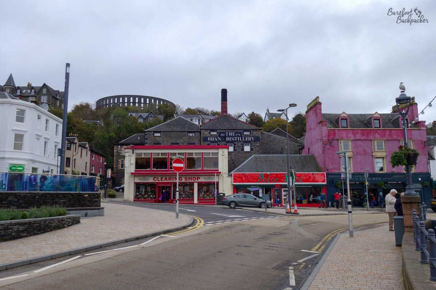 Oban town centre. Centre view, slightly in the background, is the Oban Distillery, complete with chimney. Other buildings are around, including a bright pink one on the right of shot. Road in foreground, that weird circular structure on the hilltop in the background again. What is that strange structure?