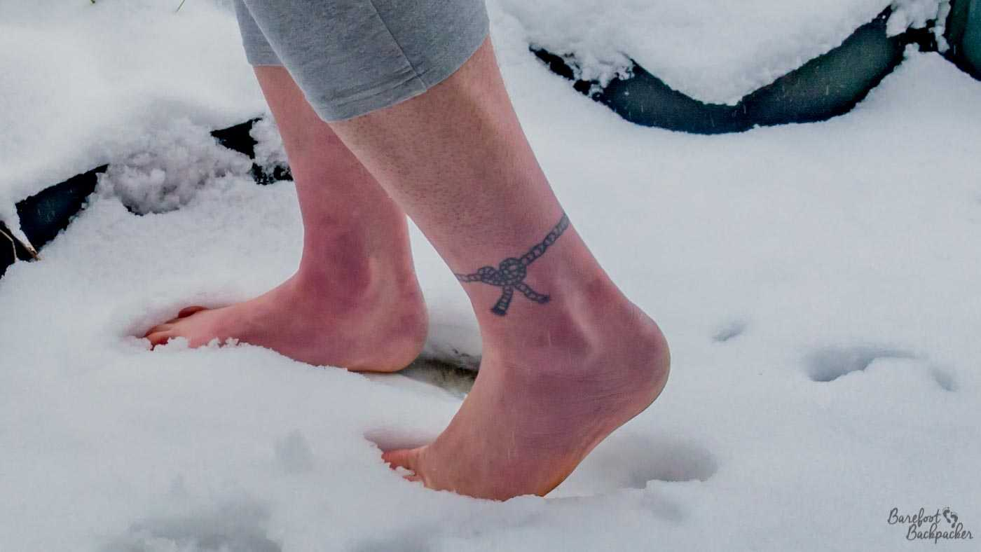 Close up of two bare feet standing in the snow of a front yard. The right foot is planted in the snow, the left foot is resting on the toes/ball of foot, with the the heel in the air. Halfway up the skin the grey jogging trousers start.