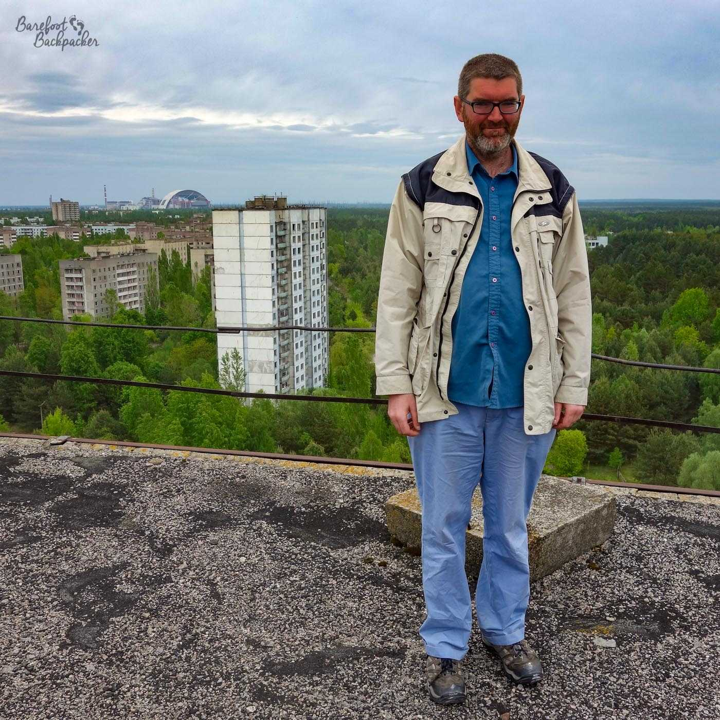A man stands on the roof of a tower block, in front of a somewhat less than convincing low metal framework serving as a barrier. He's mainly dressed in blue (shirt, trousers) and has a beige-white coat. In the background is a landscape made up almost entirely of trees. A couple of other tower blocks and tenement blocks are in the background, their upper floors just visible through the trees. In the background is a weird arch and a couple of beacons. The region is almost completely flat. This is Pripyat, Ukraine; the arch and beacon are located at the Chernobyl Nuclear Power Plant.