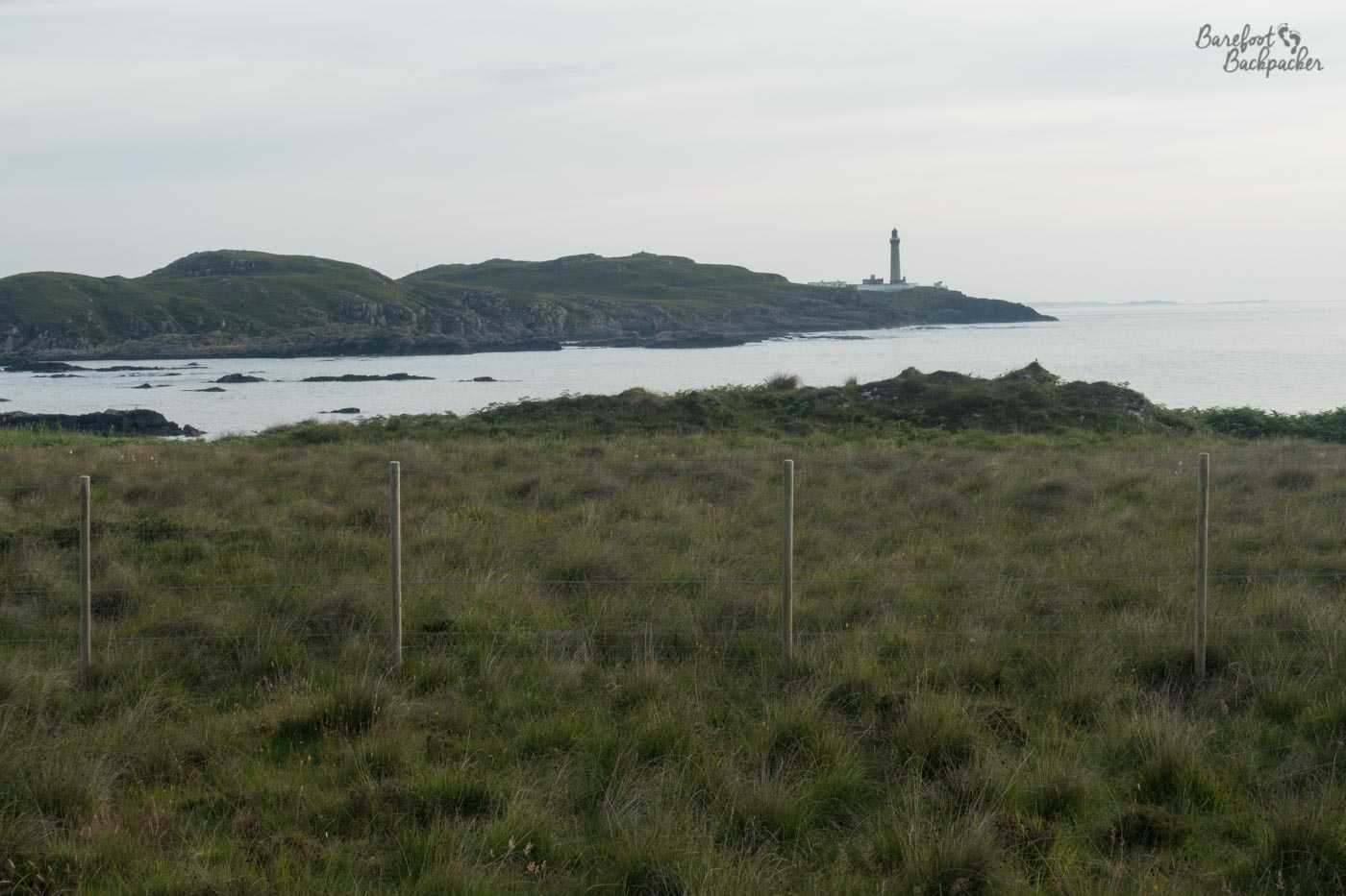 A wire fence is in the foreground. The green shrubbery land extends a little way after until it drops off a cliff. Beyond the following water inlet is a rocky outcrop, on top of which, at the far right end as it tapers into the sea, is a lighthouse, indistinctly grey at this far distance and in the slowly fading light.