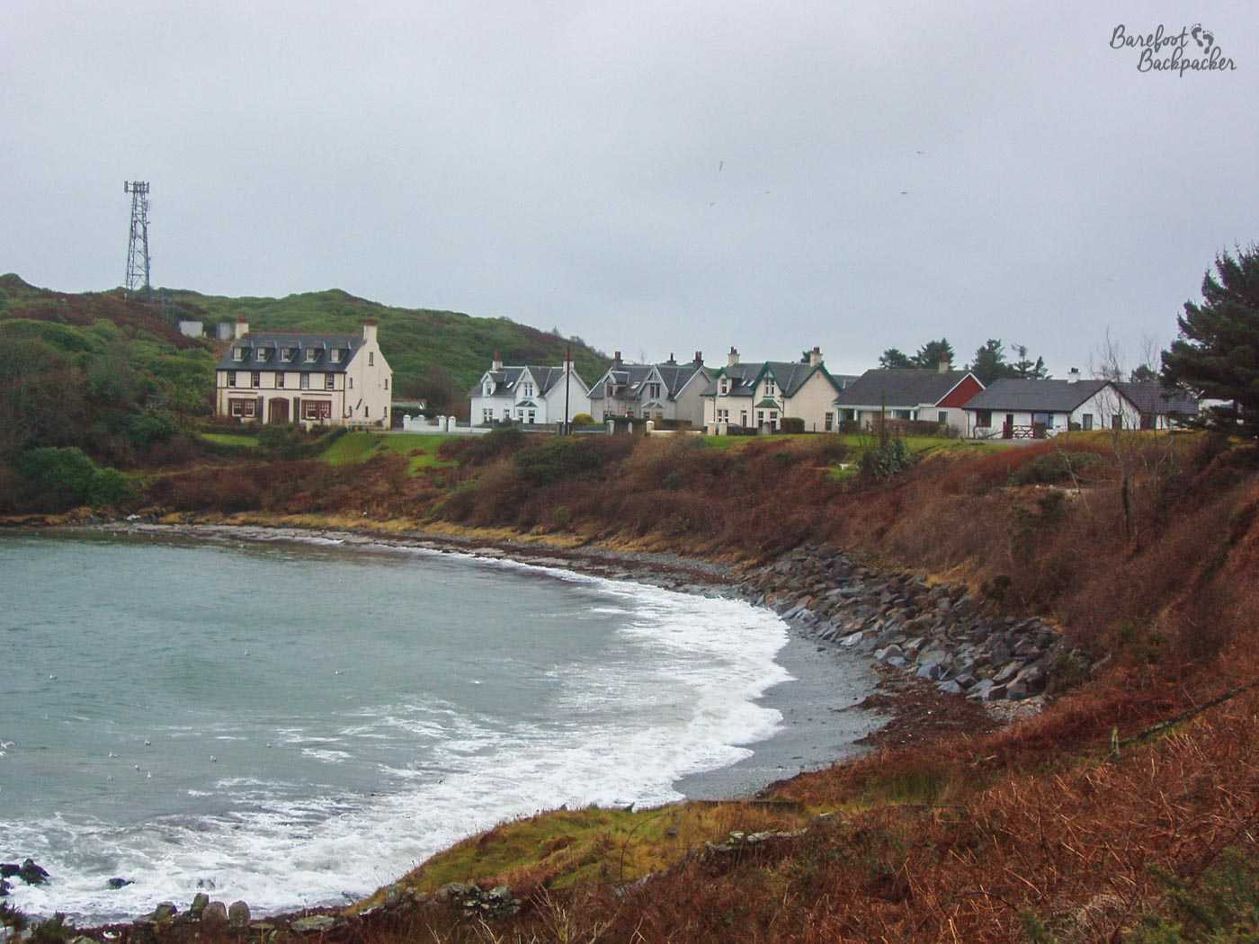 Sweeping bay comes to an end at the bottom of a short but steep rocky/grassy bank. No beach. Beyond the bank lie a row of white and beige houses. The hills continue to climb behind and away from the cottages. It is a grey, cold, windy, day.
