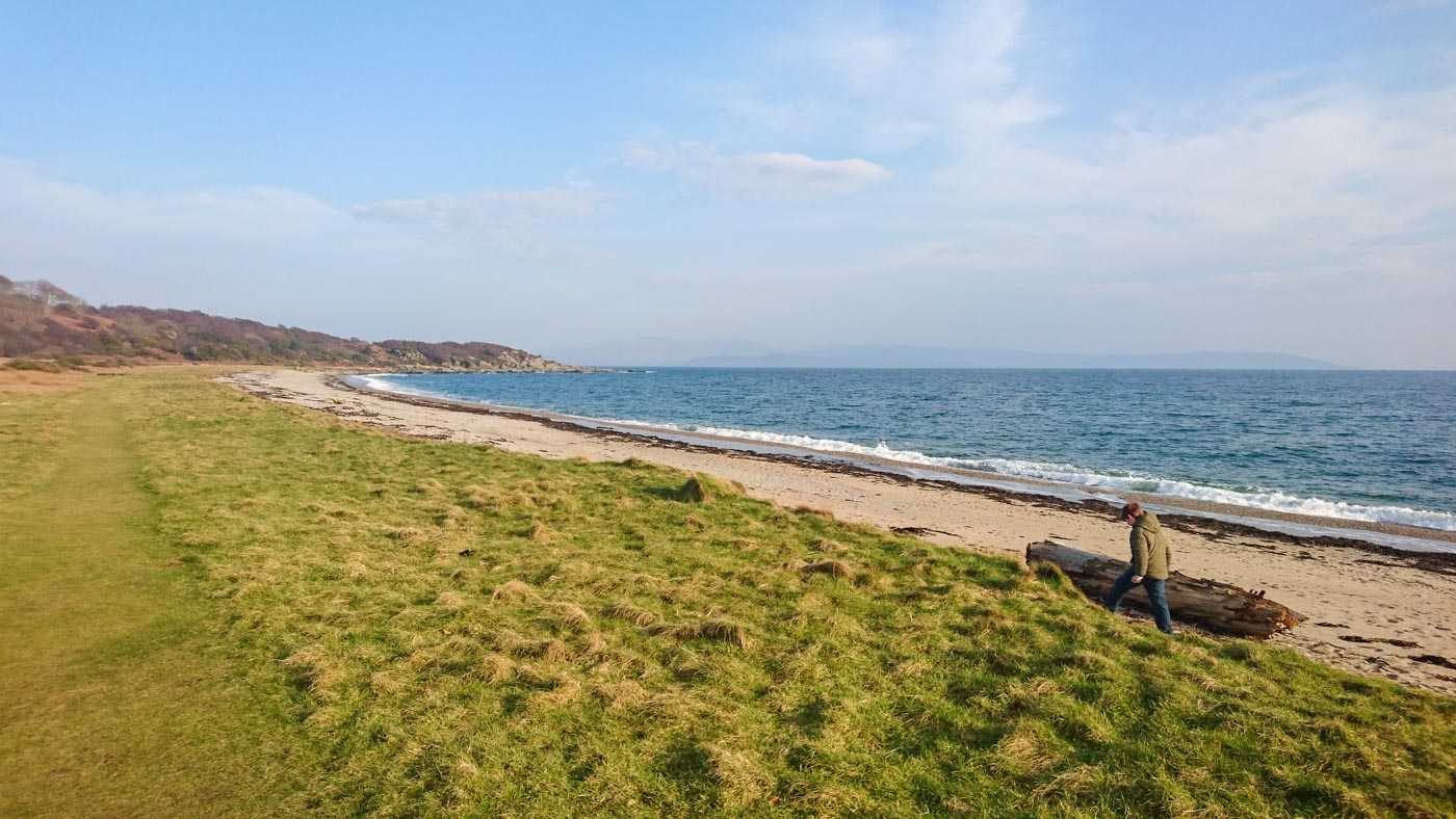 A grassy verge gives way to a narrow beach, beyond which is water. Everything curves sweepingly towards the right. A figure is walking along the beach, wrapped up warm, even tho it is a sunny day.